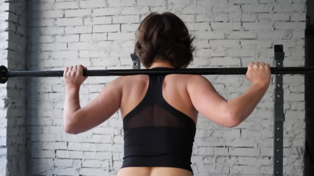 vídeos de stock e filmes b-roll de beautiful young athletic sporty woman doing back squat cardio workout in gym. back close up view - agachar se