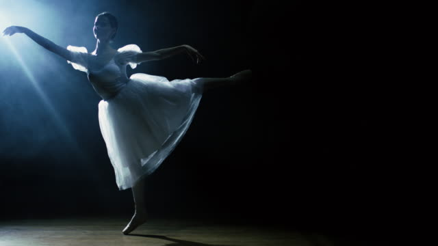 vídeos de stock e filmes b-roll de beautiful young ballerina dances gracefully in the spotlight, darkness around her. she's wearing white tutu dress that sparkles in the light. in slow motion. - tule têxtil