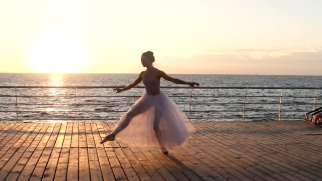 Beautiful young ballerina practices her technique, doing classic ballet pas, jumping. Landscape of sea and sun on the background