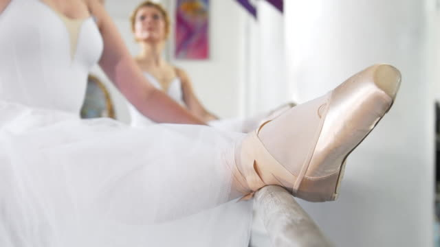 Beautiful young ballerinas on pointe exercises at ballet bar in a studio Beautiful young ballerinas on pointe exercises at ballet bar in a studio, slow motion tulle netting stock videos & royalty-free footage