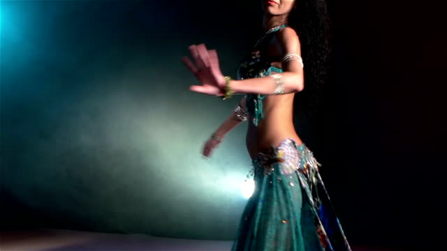 Beautiful young belly dancer continue dancing, slow motion, in smoke, blue video