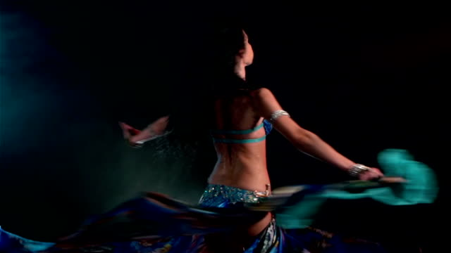 Beautiful young belly dancer dancing, slow motion, in smoke, on black video
