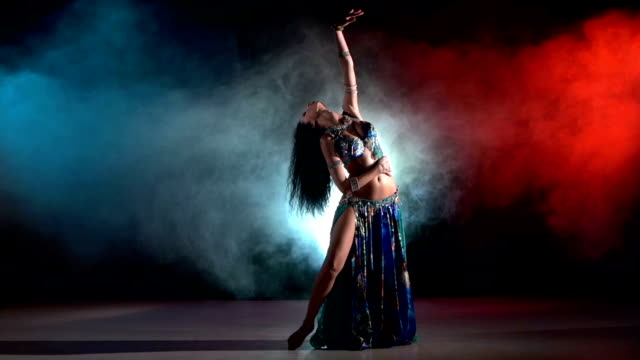 vídeos de stock e filmes b-roll de linda jovem dançarina do ventre exótica em azul fantasia de continuar a dança moderna, no preto, vermelho, fumar, câmara lenta - continuidade