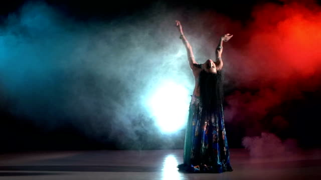 Beautiful young belly dancer in blue exotic costume go on dancing, on black, blue, red, smoke, slow motion video