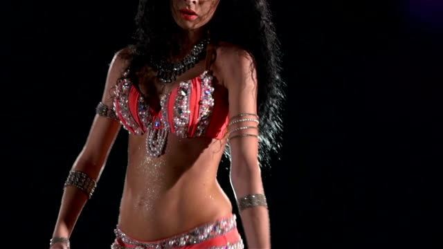 Beautiful young belly dancer starting dancing, slow motion, in smoke, on black, back light video