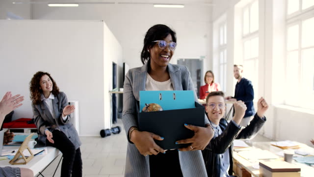 Beautiful young black female manager carrying office box, hired for a new job, multiethnic colleagues welcome and smile. video