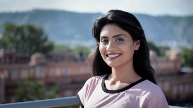 A beautiful young black haired woman smiling looking at the camera against the city landscape. A beautiful young black haired woman smiling looking at the camera against the city landscape. An attractive and pretty college or university girl student smiles while sitting in the rooftop cafe indian subcontinent ethnicity stock videos & royalty-free footage