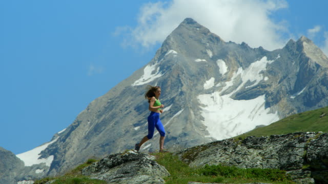 A beautiful young blond athlete running across a high altitude mountain range. video