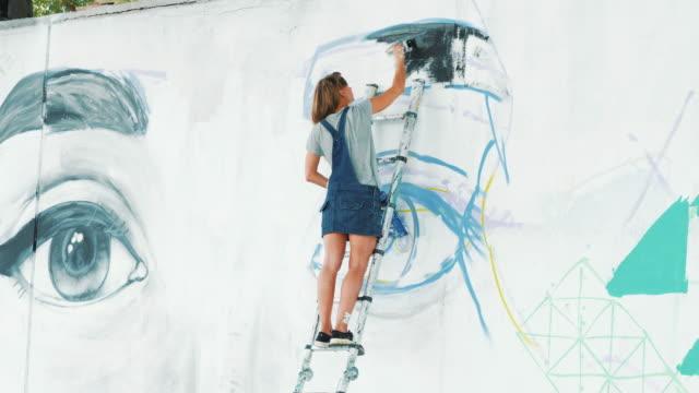 美しい若い金髪少女が都市の通りの壁にスプレーで大きな目の落書きを作るします。映画のようなトーンの映像です。創造的な芸術。デニムのオーバー オールの絵を描く才能のある学生。4 k - street graffiti点の映像素材/bロール
