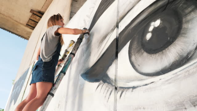 Beautiful Young Blonde Girl making graffiti of big eye with aerosol spray on urban street wall. Cinematic toned footage. Creative art. Talented student in denim overalls drawing picture. 4k