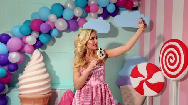 vídeos y material grabado en eventos de stock de una hermosa jovencita rubia en un vestido rosado hace un selfie con una piruleta grande. - galleta dulces