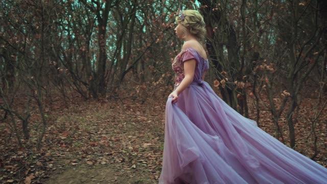 vackra unga blonda prinsessan promenader i lila frodig klänning med ett långt tåg - aftonklänning bildbanksvideor och videomaterial från bakom kulisserna