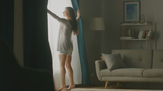vídeos de stock e filmes b-roll de beautiful young brunette opens curtains to let morning sunlight in, dances happily across cozy living room. side view of attractive girl rising early and greeting new day. slow motion - open window