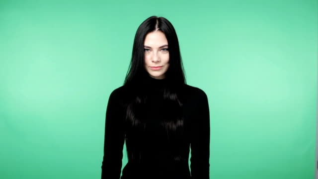 beautiful young brunette woman in a black shirt smiling and looking into the camera, chroma key green screen background - top nero video stock e b–roll