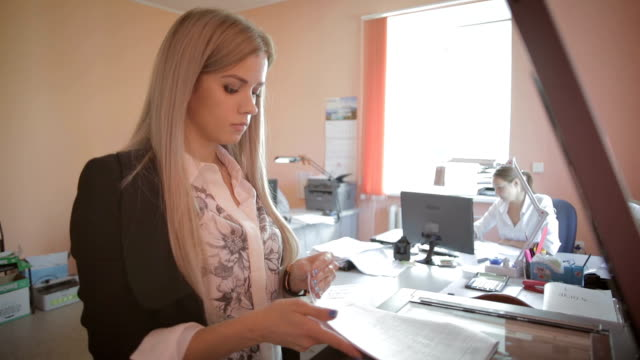 beautiful young business woman making photocopies in office stock footage video - служащая стоковые видео и кадры b-roll