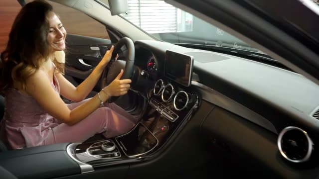 Beautiful young businesswoman buying new car. Happy in slow-mo Beautiful young businesswoman buying new car. A gift to a young wife from her beloved husband. Slow-mo luxury car stock videos & royalty-free footage