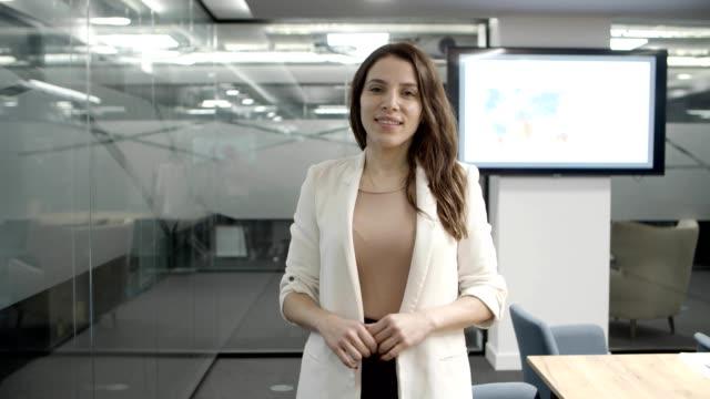 vídeos de stock, filmes e b-roll de bela jovem empresária olhando para a câmera - plano médio