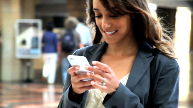 Beautiful young businesswoman on iPhone. People in BG. Texting laughing. video