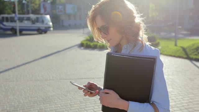 Schöne junge Geschäftsfrau trägt blaues Hemd und mit modernen Smartphone während des Gehens in der Pause in der Stadt, professionelle weibliche Arbeitgeber schreiben SMS auf Handy außerhalb – Video