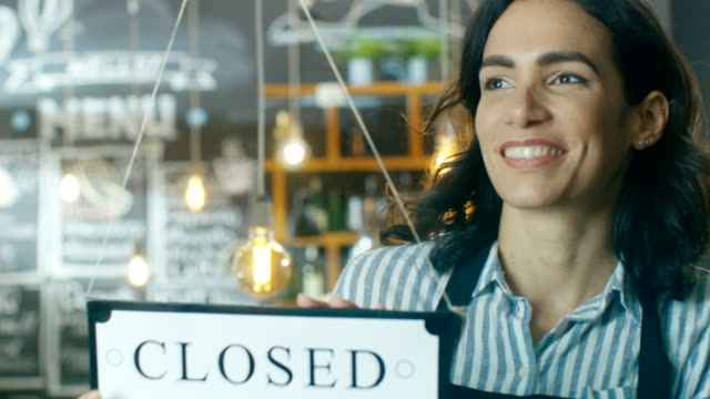 beautiful young cafe owner turning door sign from close to open and welcoming new customers into her modern looking stylish coffee shop. - open sign stock videos & royalty-free footage