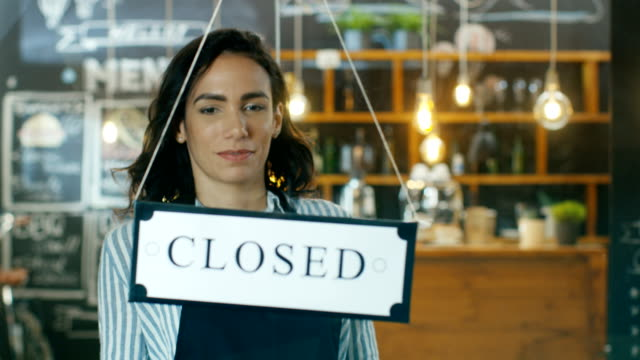 beautiful young cafe owner turning storefront sign from close to open and welcoming customers into stylish coffee shop. big city with traffic and people visible in window reflection. slow motion. - open sign stock videos & royalty-free footage