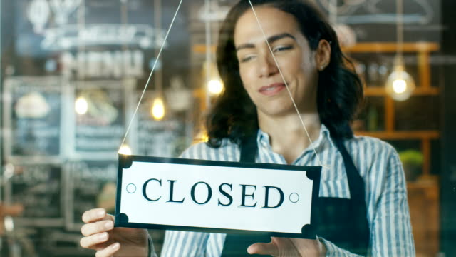 beautiful young cafe owner turning storefront sign from close to open and welcoming her new customers into her modern looking stylish coffee shop. - open sign stock videos & royalty-free footage
