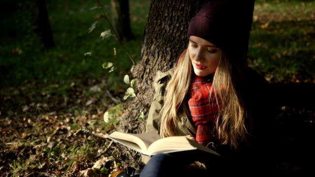 Beautiful young caucasian girl reading a book in the autumn park. video