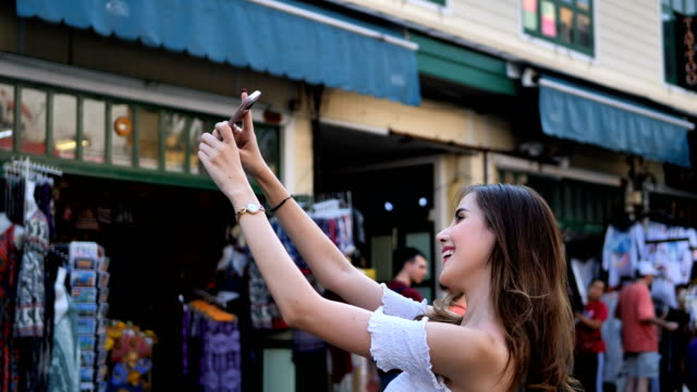 Beautiful young caucasian taking selfie in city centre are walking Khaosan Road walking street in evening at Bangkok, Thailand. Happy female traveler and tourist concept.