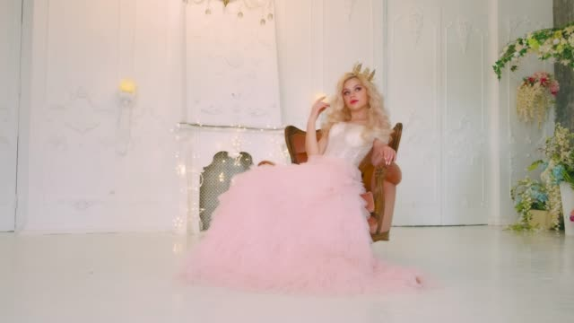 Beautiful young charming pretty woman sitting in chair. vintage antique medieval pink lush dress. Backdrop classic room interior luxury castle. white studio. Long Blonde wavy flowing hair golden crown