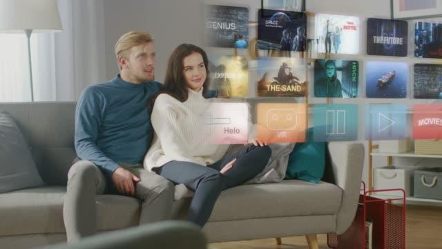 vackra unga par sitter på en soffa hemma och välja en film att titta på en futuristisk hologram skärm. - konstkultur och underhållning bildbanksvideor och videomaterial från bakom kulisserna