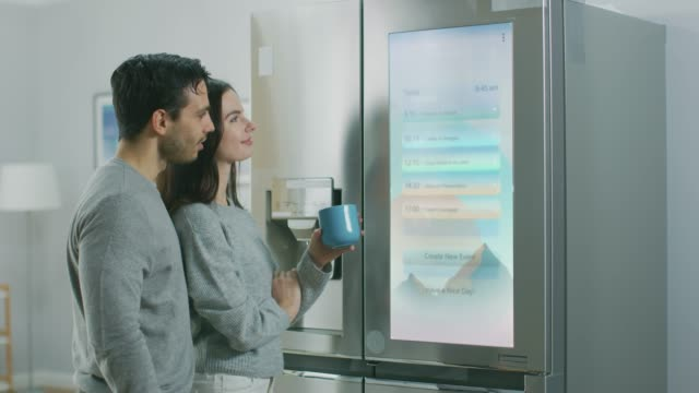 Beautiful Young Couple Drink Morning Coffee in the Kitchen. They Check the Weather Forecast and a To Do List on a Smart Fridge at Home. Apartment is Bright and Cozy.