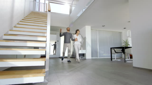 Beautiful Young Couple Enters Their Newly Purchased House, They're Very Happy and Their Home is Bright and Modern. video