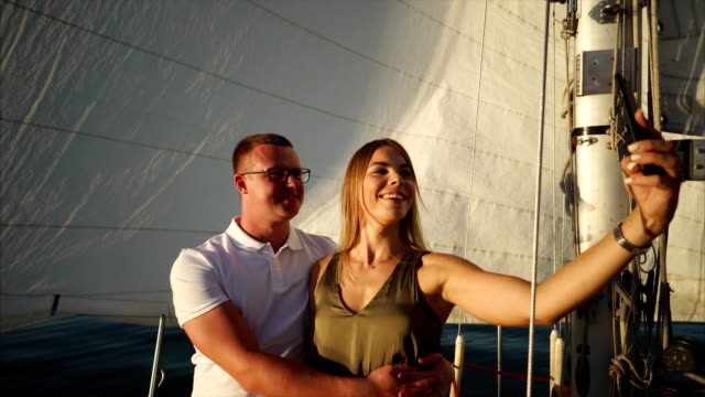 Beautiful young couple is taking selfie on board a yacht. video