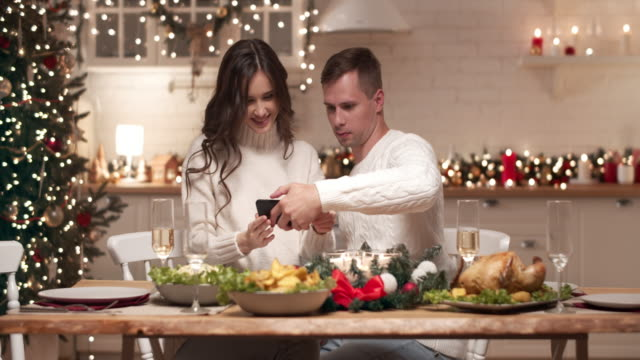 Beautiful young couple sitting at the Christmas table waiting for friends. Young people make a joint selfie on the phone camera they send Christmas photos to their friends and relatives. Beautiful young couple sitting at the Christmas table waiting for friends. Young people make a joint selfie on the phone camera they send Christmas photos to their friends and relatives. treedeo christmas stock videos & royalty-free footage