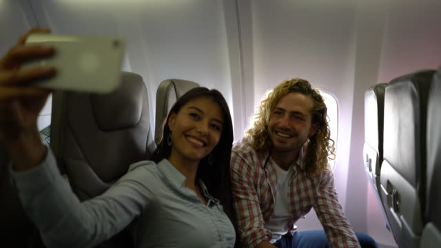 beautiful young couple taking a selfie while seating at the airplane both smiling - south america travel stock videos and b-roll footage