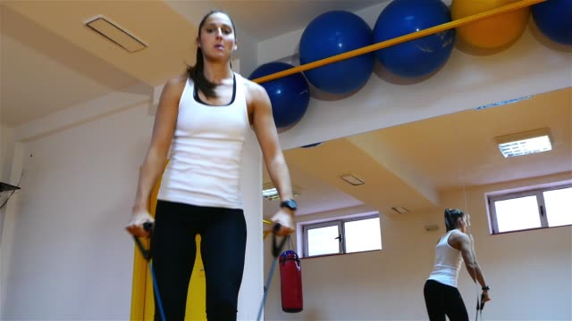 Beautiful young dark hair girl doing exercises in the gym. video