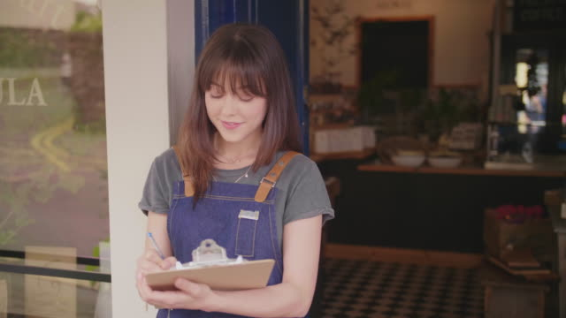 Beautiful Young Deli Owner Writing In Clipboard Outside Store video
