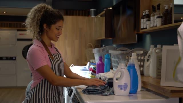 Belle jeune employé à une laverie automatique, pliage des chemises souriant - Vidéo