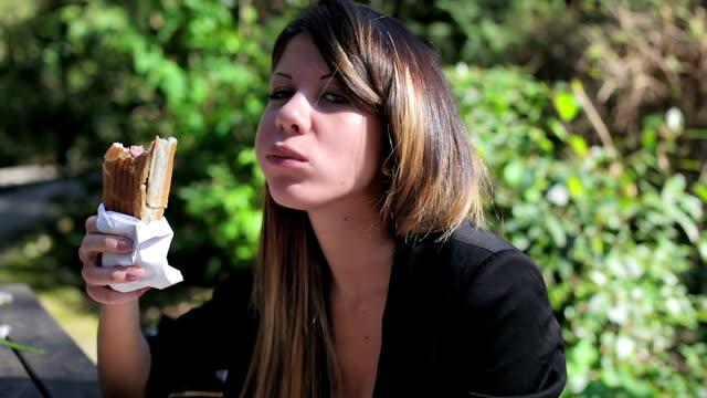 vídeos de stock, filmes e b-roll de bela jovem animada mulher comer um cachorro-quente num parque - alimento cru