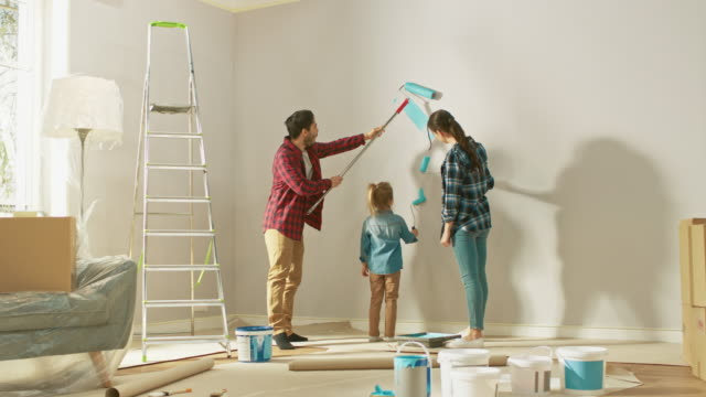 vídeos de stock e filmes b-roll de beautiful young family are showing how to paint walls to their adorable small daughter. they paint with rollers that are covered in light blue paint. room renovations at home. - bricolage