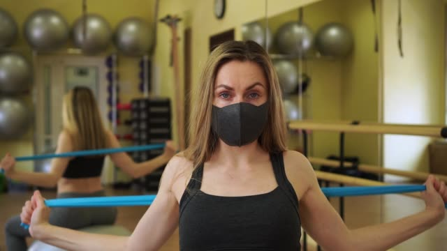 stockvideo's en b-roll-footage met de mooie jonge vrouwelijke atleetvrouw die zwart beschermend masker draagt doet blauwe oefeningen van de rubberweerstandsband in lege gymnastiek tijdens coronavirusquarantaine - mirror mask