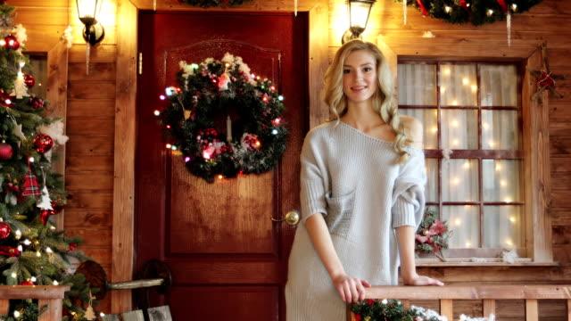 schöne junge weibliche modell mit langen lockigen blonden haaren auf weihnachten und neujahr dekorationen hintergrund. - wohngebäude innenansicht stock-videos und b-roll-filmmaterial