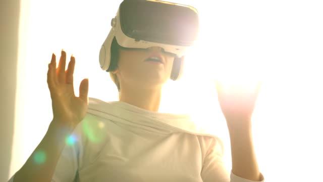 beautiful young female playing game in vr glasses - rzeczywistość witrualna filmów i materiałów b-roll