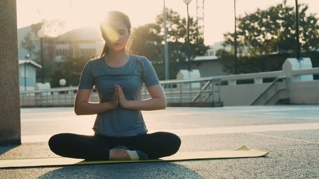 Beautiful young female practicing yoga, sitting in padmasana on a yoga mat, sport and health concept. Beautiful young female practicing yoga, sitting in padmasana on a yoga mat, sport and health concept. lotus position stock videos & royalty-free footage
