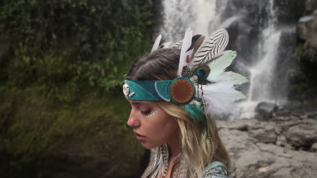 Beautiful young female standing near the falling stream full of dreams