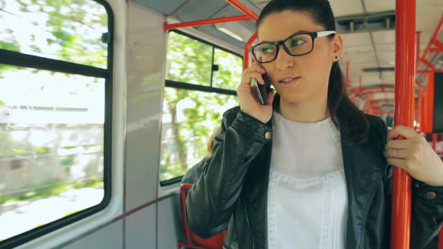 Beautiful young female talking on mobile phone on train. video