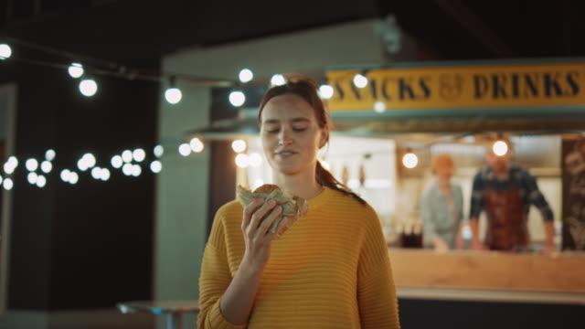 stockvideo's en b-roll-footage met mooie jonge vrouwelijke wandelingen weg van een food truck met een heerlijke verse rundvlees hamburger. ze is blij met hew eten en neemt een biet. commercial kiosk verkoopt straatvoedsel op een moderne koele straat. - foodtruck