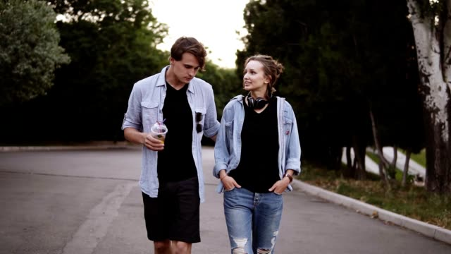 beautiful young friends both in black t shirts and blue shirts are walking by park in the evening dusk. talking, dating, summer time. front view - top nero video stock e b–roll