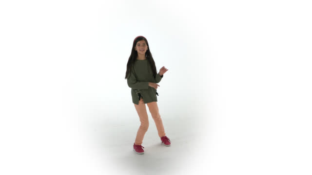Beautiful young girl dancing while facing camera at a studio with white background