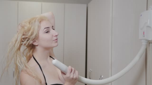 Beautiful young girl dries hair with a hairdryer after spa treatments